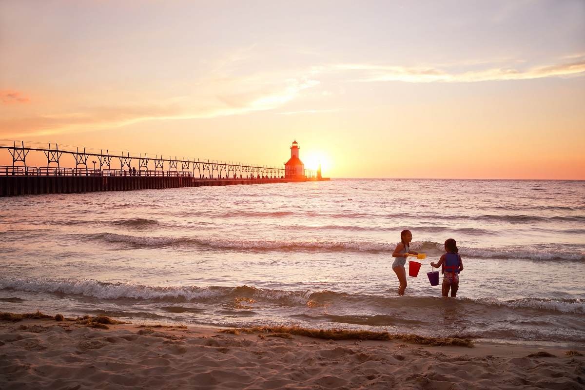 kids playing by the shore with a lighthouse